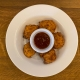 5 pumpkin fritters arranged around a container of tomato ketchup